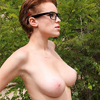 busty-girl-with-glasses-tanning-in-nature
